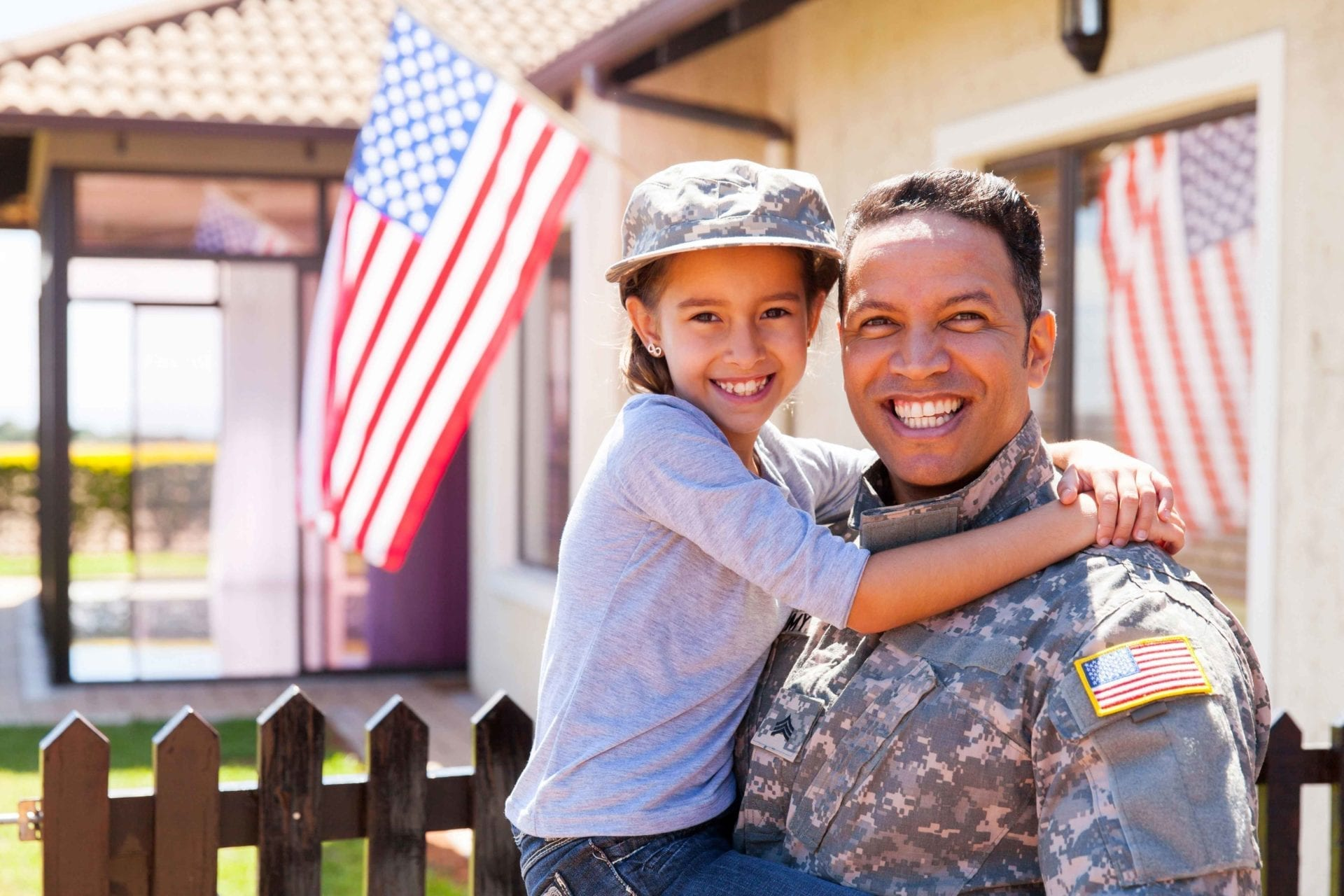Man in an service uniform holding a child with an American flag in the background.