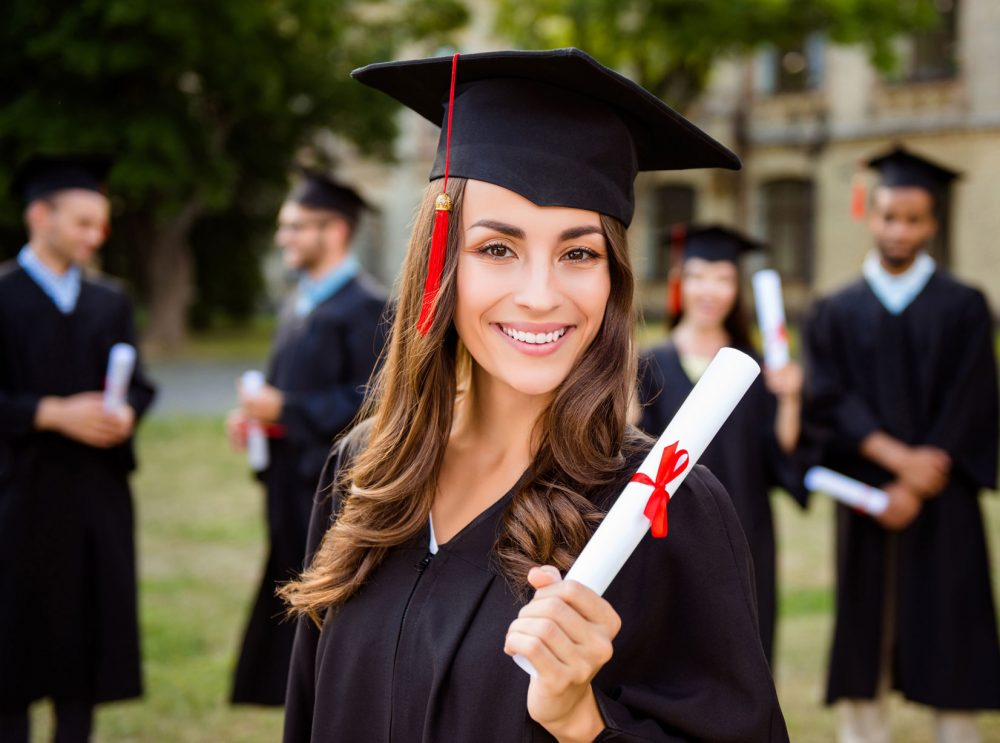 Female graduate smiling and holding her diploma.
