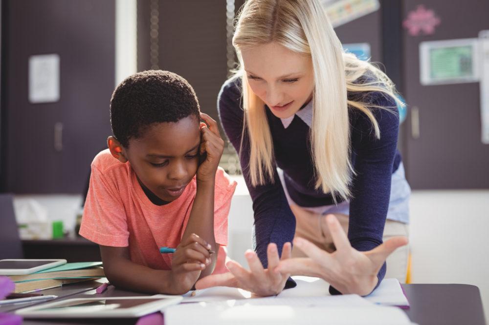 Teacher helping schoolgirl with her homework in classroom